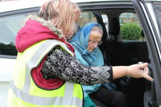 ECL care staff opening the car door for one of their customers