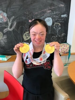 ECL customer Rosa showing off her gold medals
