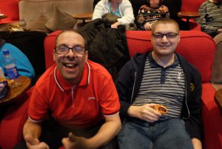 Two customers with learning disabilities sitting down in Everymand Cinema waiting for the screening.