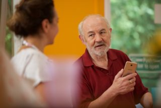 Older person being taught how to use a mobile phone by a care worker.