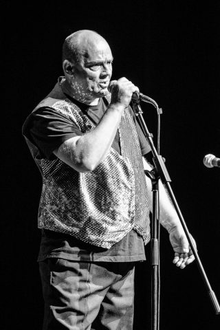 Male adult with a learning disability sinding into a microphone on a stand.