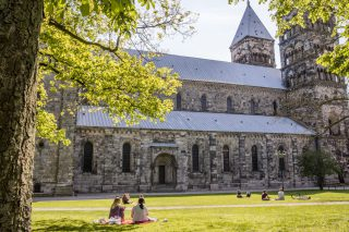 Two people enjoying a picnic on a hot summer's day, sitting on lush green grass outside a beautiful church.