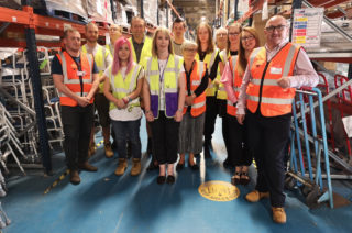 Team photo of Community Equipment staff at the equipment warehouse.