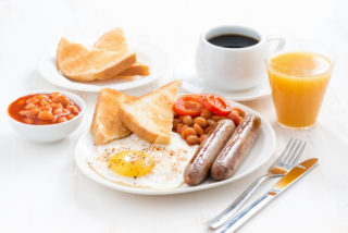 Picture of a full English breakfast with coffee and orange juice on a white background