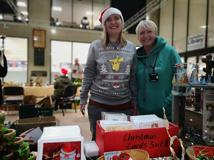 One ECL customer and one ECL staff member standing side by side smiling towards the camera at the Christmas Fayre.