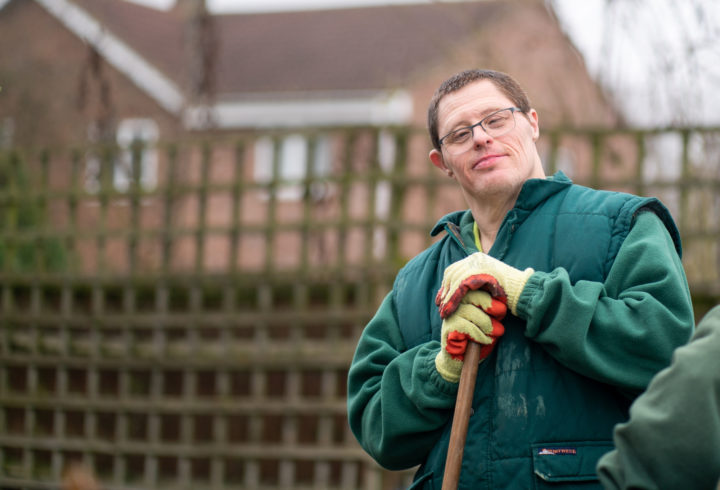 Male customer of ECL with learning disabilities taking a moment to stop what he is doing (gardening) to look into the camera and smile.