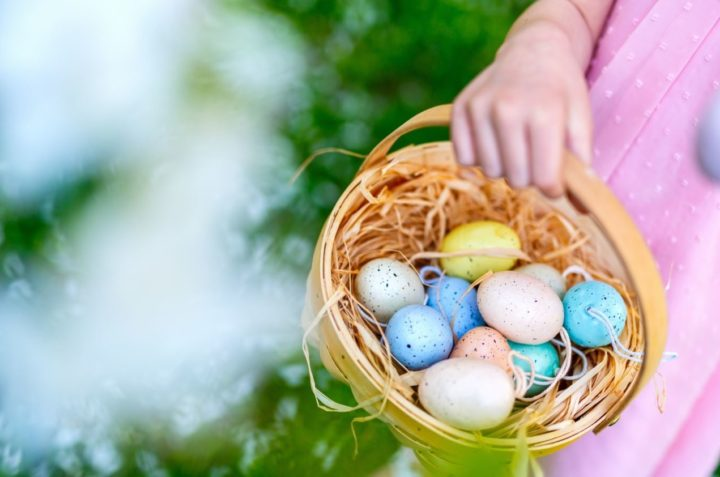 Close up shot of a hand holding a small basket, full of colourful easter eggs.