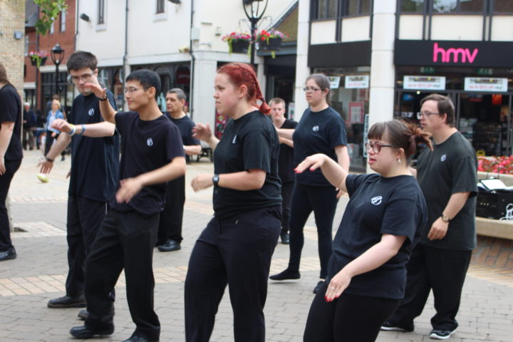 Group of adults with learning disabilities dancing in Colchester Culver Square.