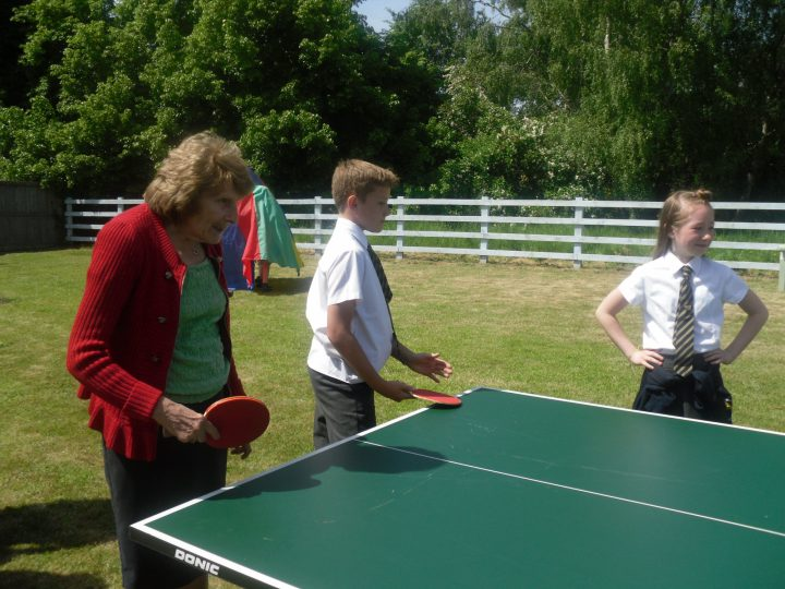 Older aged female playing table tennis with two children from the local school.