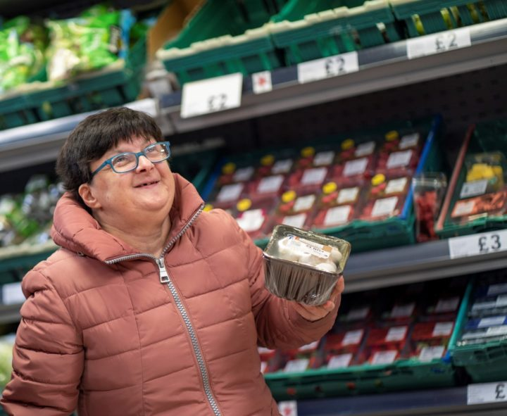 Happy female shopping in a supermarket amongst the vegetable aisle.