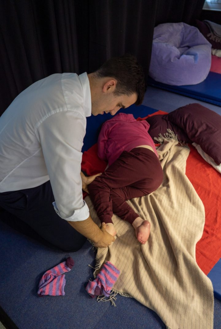 ECL Clinical Team member performing physiotherapy on a customer's leg lying down on a mat.