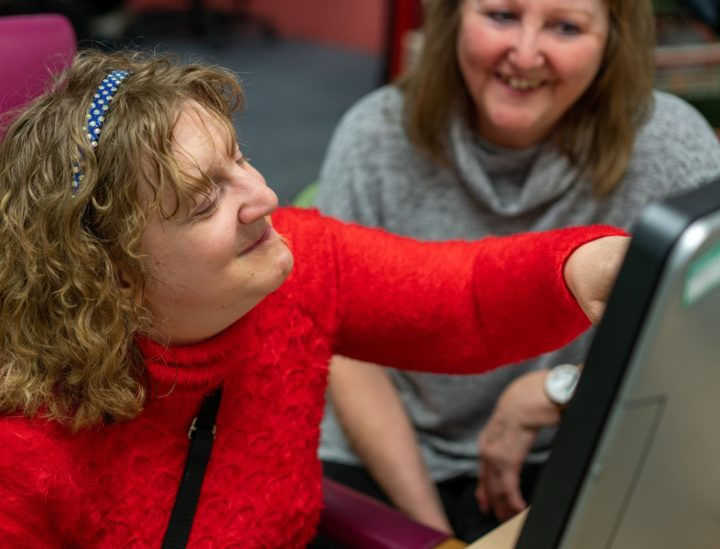 Blonde ECL customer wearing a red jumper is interacting with a touchscreen computer, directed by a brunette ECL staff member sitting to the side.