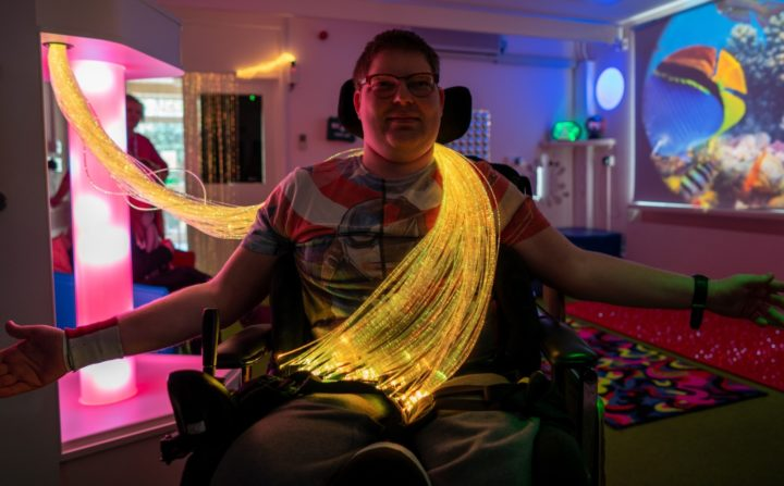 Male ECL customer sitting down within a sensory room with a big bunch of yellow fibre optic strings draped over his left shoulder.