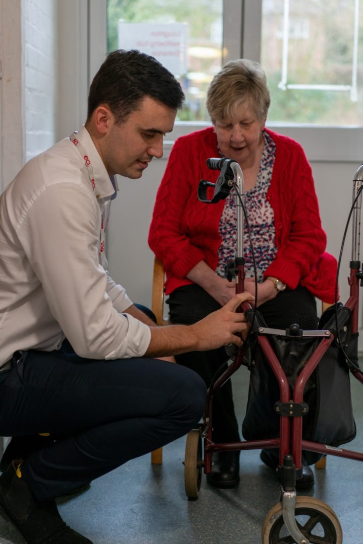ECL Clinical Team member performing physiotherapy on a customer's leg sitting down on a chair.