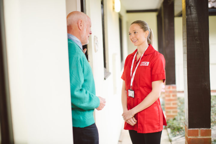 ECL staff member talking to an elderly customer at their home address by the front door.