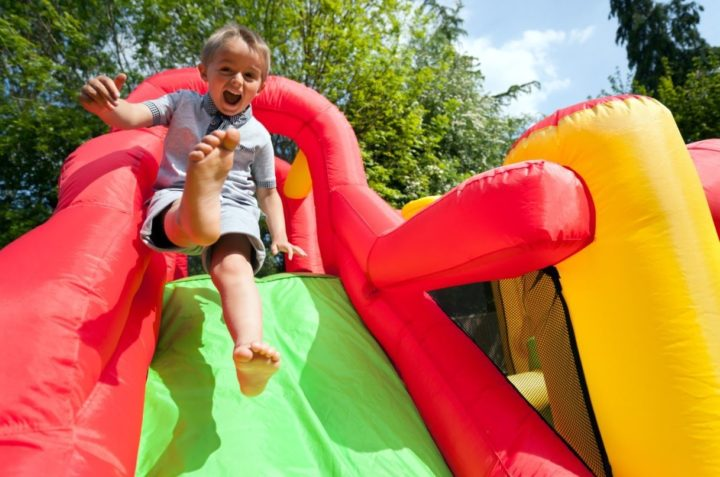 Young boy overjoyed looking into the camera laughing whilst jumping down a green, red and yellow bouncy castle slide.