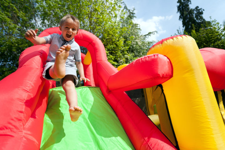Young boy on a bouncy castle slide