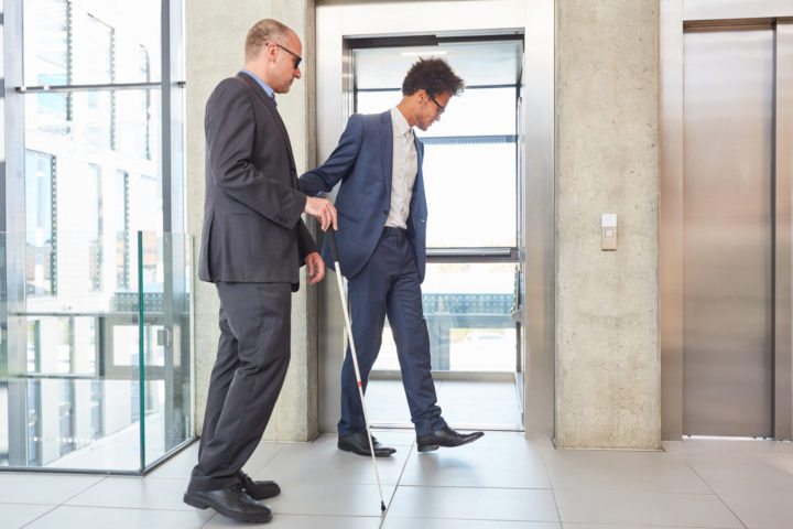 A person with impaired vision being guided to an elevator by a business man
