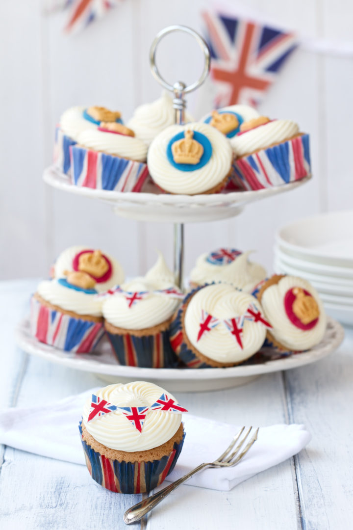 Plate of iced cupcakes decorated in a royal theme