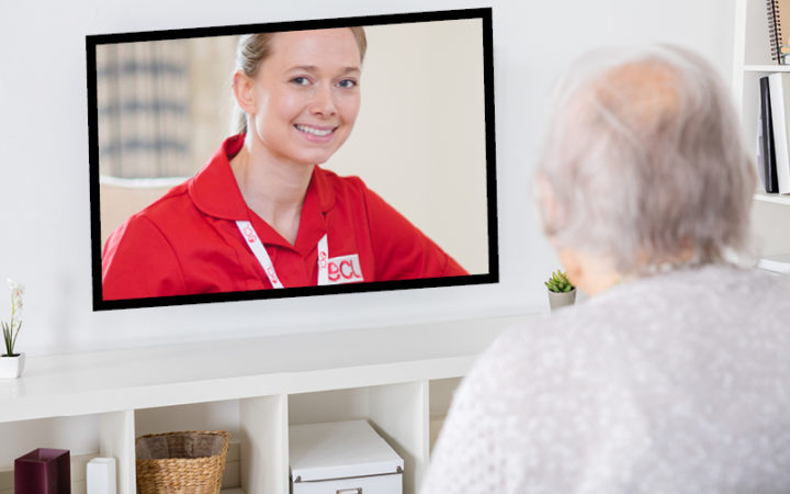 Older adult facing the television, video chatting to their care worker.