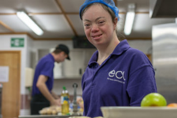 Young female with down syndrome volunteering in a café canteen.