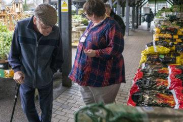 Customer volunteering at a garden centre and serving an elderly gentleman.