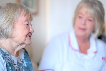 Doris and Jan (carer and customer) sit and chat on a sofa