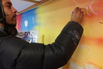 Graffiti artist works on colourful interior wall with white pen.