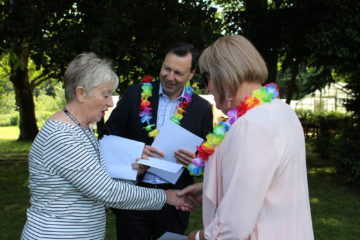 Sensory impaired volunteers celebrated by receiving ECL certification in wooded area.
