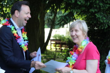 ECL sensory impaired volunteer steps up to accept her certificate from laughing male.